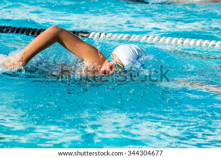 Close up action shot of Teen boy swimming freestyle at swimming lesson. - stock photo