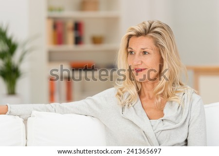 Close up Adult Blond Woman Sitting on White Couch While Looking and Smiling at her Right Side - stock photo