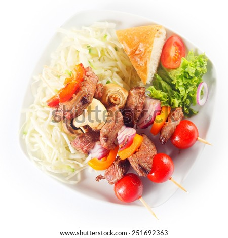 Close up Aerial Shot of Appetizing Kebabs on White Plate with a Slice of Bread and Fresh Veggies. Isolated on White Background. - stock photo