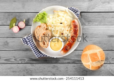 Close up Aerial Shot of Breakfast Recipe on Wooden Table with Sausage, Vegetable Salad, Bread and Sauce on White Plate - stock photo