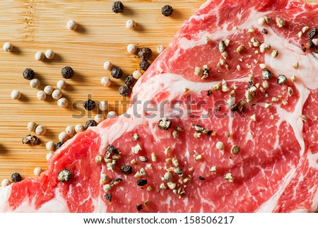 Close up aged beef ribeye steak with black and white pepper on bamboo chopping board - stock photo