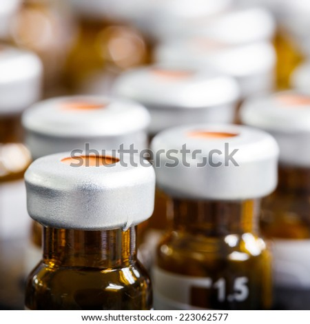 Close up amber color vials with inserts and crimp septum caps - stock photo