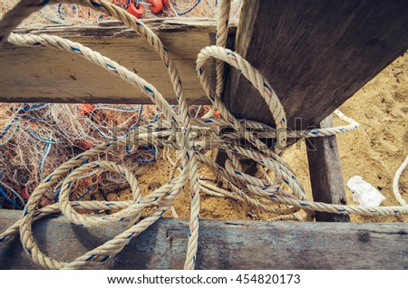close up and selective focus,traditional fishing net over blurred background, wooden fisherman cottage and rope - stock photo