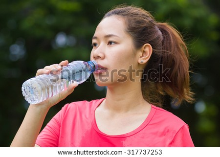 close up and selective focused of asian sporty woman try to take a bottle of water for drinking after exercising for freshness:woman relax and rest  after workouts at the park.woman fitness concept - stock photo