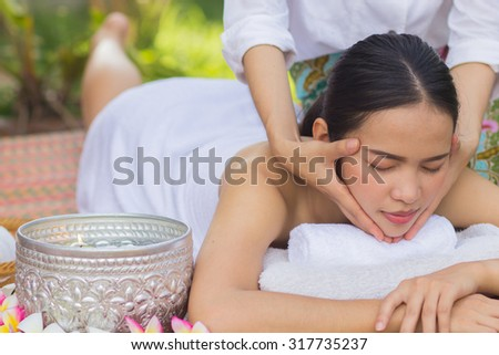 close up and selective focused on young beautiful asian woman are massaging:Thai woman in spa treatment :woman relaxing wellness concept.natural outdoors spa treatment concept :soft focused concept. - stock photo