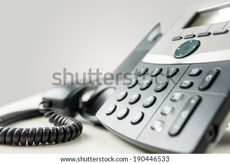 Close up angled view of a landline telephone instrument with a number pad and the handset or receiver off the hook in a communications concept. - stock photo