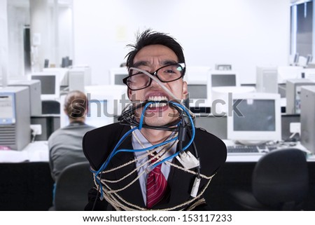 Close-up angry businessman tied in rope and cable at office - stock photo