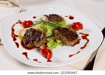 Close up Appetizing Garnished Grilled Meat Dish with Herbs, Lettuce and Tomato Slices on White Plate, Served on the Table. - stock photo
