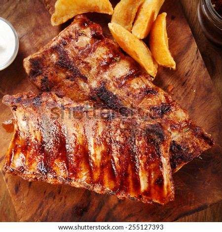 Close up Appetizing Grilled Pork Rib on Top of Wooden Cutting Board with Fried Potatoes. - stock photo