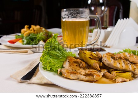 Close up Appetizing Main Dishes and Mug of Beer on White Dining Table at Restaurant - stock photo