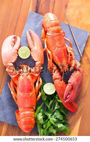 Close up Appetizing Ready to Eat Cooked Lobsters Duo on a Cutting Board with Lime and Parsley, Served on a Wooden Table. - stock photo
