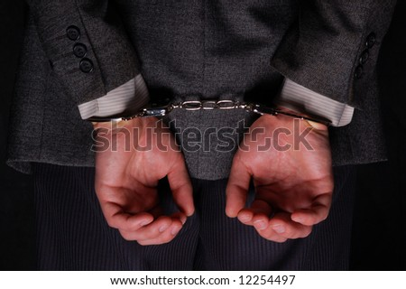 Close-up. Arrested businessman handcuffed hands at the back - stock photo