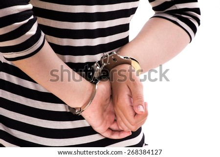 Close-up. Arrested person handcuffed wearing stripes. - stock photo