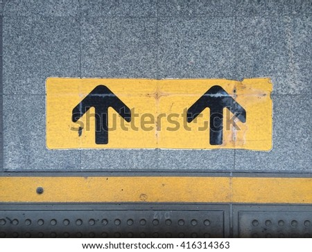 Close up Arrow sign on floor at the sky train station, Bangkok, Thailand - stock photo