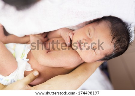 Close-up Asian baby girl sleeping on a hand - stock photo