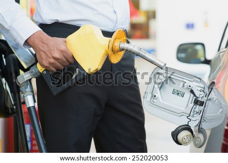 Close up Asian man pumping gasoline fuel in car at gas station. - stock photo