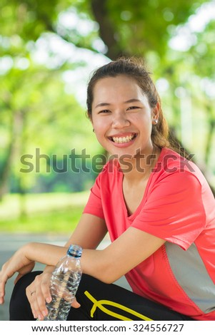 close up asian sport woman smile with a bottle of water for drinking after exercising for freshness : woman resting after workouts or jogging or running at the park outdoor.woman exercise concept - stock photo