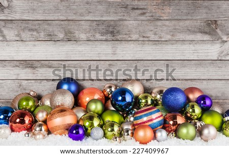 Close up Assorted Colored Christmas Balls Decorations on Snow with Vintage Wooden Wall Background. - stock photo