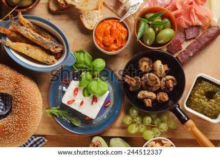 Close up Assorted Tapas Foods on Wooden Table, Emphasizing Cheese, Mushrooms, Meats, Bread, Olives and Sauce. - stock photo