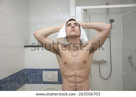 Close up Attractive Young Bare Muscular Man Drying his Hair after Taking Shower Looking Up - stock photo