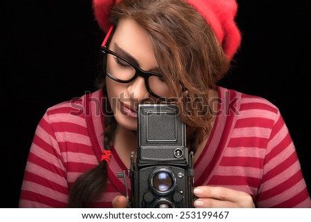 Close up Attractive Young Woman in Red Trendy Outfit Capturing Photo Using Vintage Camera. Isolated on Black Background with Copy Space - stock photo