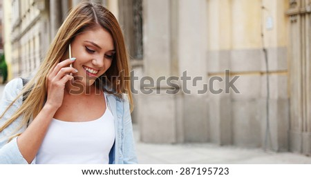 Close up Attractive Young Woman Using her Mobile Phone While Walking at the Street Alone. - stock photo