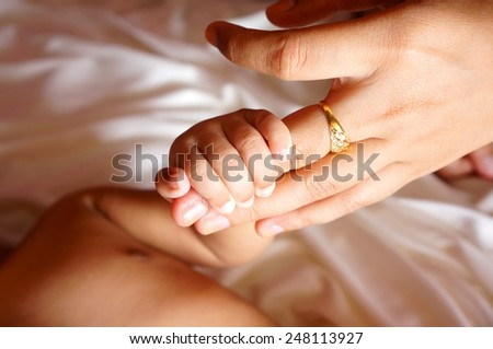 Close up baby hands holding mother's finger (DOF) - stock photo