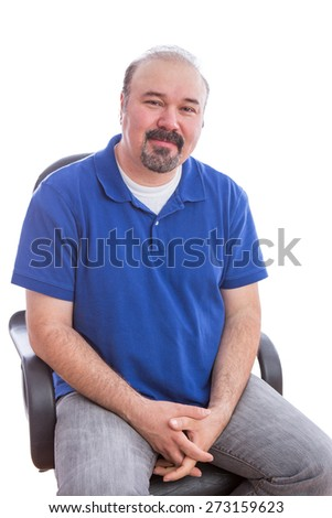 Close up Bearded Man in Blue Polo Shirt, Sitting on a Chair in an Optimistic Emotion and Looking at the Camera. Isolated on White Background. - stock photo