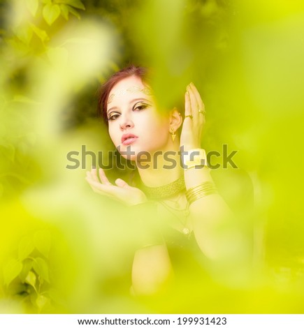 Close-up - beautiful makeup girl wearing black tunic and an antique jewels, green leaves around - stock photo