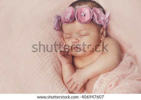 Close-up beautiful sleeping baby girl. Newborn baby girl, asleep on a blanket. A portrait of a beautiful, seven day old, newborn baby girl wearing a large, fabric rose headband. Closeup photo - stock photo
