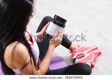 Close-up beautiful sporty young woman with jar of protein. - stock photo