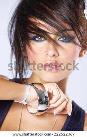 Close up Beautiful Young Woman in Funky Hair with Silver Bracelet Isolated on Gray Background. - stock photo