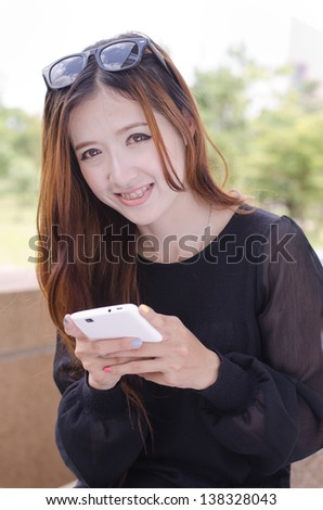 Close up beautiful young woman using a mobile phone - stock photo