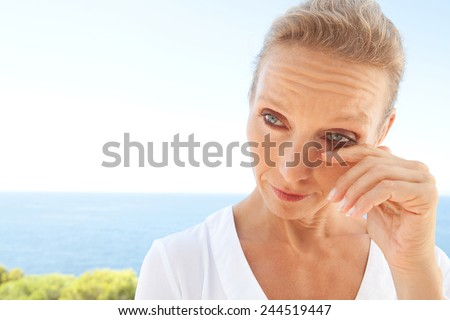 Close up beauty portrait of a senior mature healthy woman with blue eyes and flawless skin crying and drying up her tears, worried and emotional. Mature and aging face with a sad expression, outdoors. - stock photo