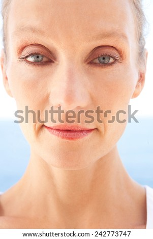 Close up beauty portrait of a senior mature healthy woman with blue eyes and flawless skin looking at the camera. Mature and aging face with a serene and confident expression, outdoors. - stock photo
