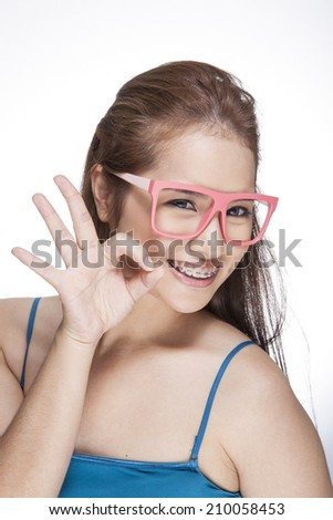 Close-up, beauty portrait of a smiling, beautiful, young woman showing an OK sign.  - stock photo