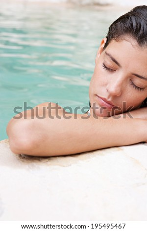 Close up beauty portrait of a thoughtful young woman leaning on the stone edge of a clear and natural spa swimming pool enjoying a summer holiday and relaxing outdoors. Health and beauty lifestyle. - stock photo