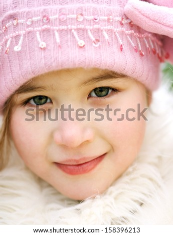 Close up beauty portrait of a young child girl wearing a winter coat, woolly hat and gloves, smiling to the camera during a cold winter day, outdoors. - stock photo