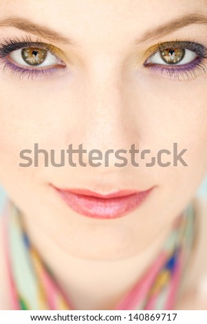 Close up beauty portrait of a young woman face wearing blue and yellow make up eyeshadow cosmetics looking at camera and softly smiling. - stock photo