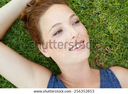 Close up beauty portrait of an attractive joyful young beautiful woman laying down on green grass in a park, relaxing on a summer holiday, smiling. Healthy living, Well being lifestyle, exterior. - stock photo