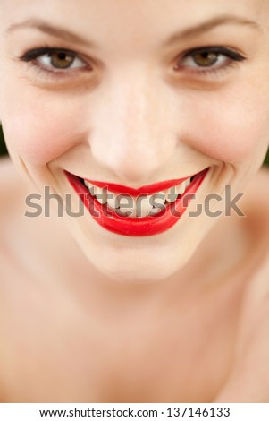 Close up beauty portrait of an attractive young woman and wearing bright red lipstick cosmetics on her lips, smiling. - stock photo
