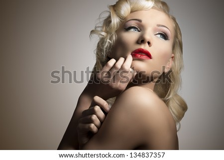 close-up beauty portrait of pretty blonde girl with retro hair style and make-up in diva pose - stock photo