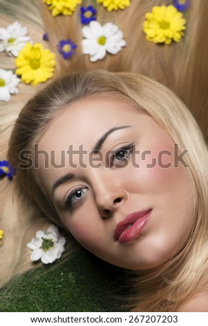 close-up beauty portrait of sensual blonde woman with perfect skin and natural make-up lying on green grass with some colorful flowers in smooth and long hair  - stock photo
