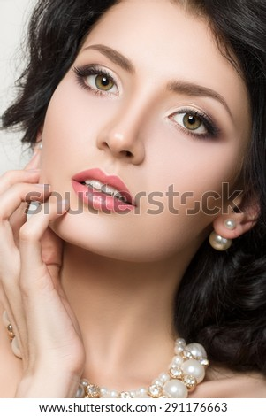 Close-up beauty portrait of young pretty brunette model with beautiful make-up. - stock photo