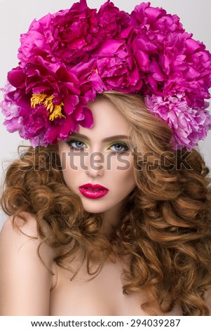 Close-up beauty portrait of young pretty girl with flower wreath in her hair wearing bright pink lipstick. Bright modern summer makeup. Beauty, spa and skincare concept - stock photo
