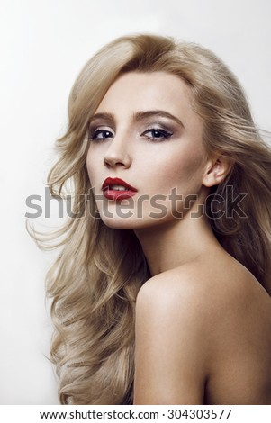 Close-up beauty shot of a beautiful young blonde women with the wind in the hair and sensuality in the eyes. Developed from RAW. Retouched with special care and attention. - stock photo