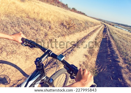 Close up bicycle rider's hands  on a mountain bicycle handlebar. - stock photo