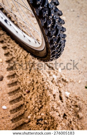 Close up bike tire shot on the beach . Outdoors, nautical, biking, urban living, cross fitness and adventure background concept - stock photo