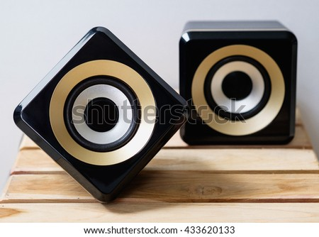 Close up black and golden speakers, sound sub woofer equipment, modern bluetooth speaker on wooden background - stock photo