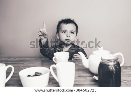 Close-up black and white candid natural portrait of cute adorable little boy toddler in kitchen indoors making funny face, lifestyle documentary style, grainy film effect - stock photo